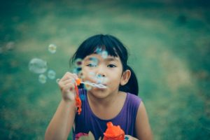 girl blowing soap bubbles